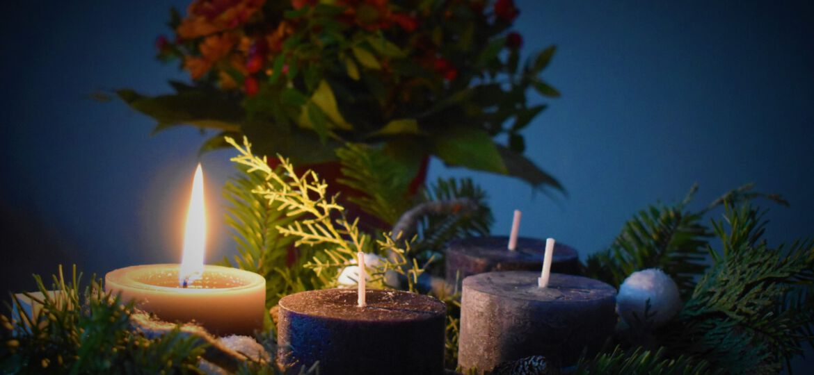 lighted candle beside another 3 candles
